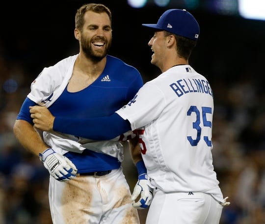 Los Angeles Dodgers' Chris Taylor, left, gets mobbed by center fielder Cody Bellinger after Taylor hit a walk-off solo home run during the 10th inning of a baseball game against the Colorado Rockies in Los Angeles, Tuesday, Sept. 18, 2018. (AP Photo/Alex Gallardo)