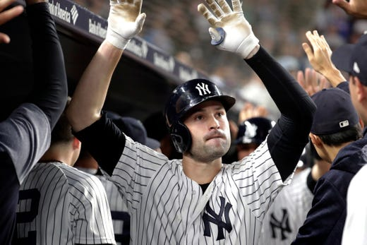 New York Yankees' Neil Walker is congratulated by teammates after hitting a three-run home run off Boston Red Sox relief pitcher Ryan Brasier during the seventh inning of a baseball game Tuesday, Sept. 18, 2018, in New York.