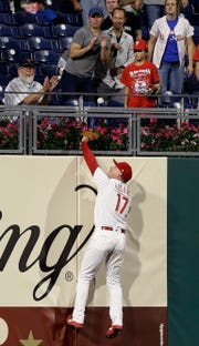 Philadelphia Phillies left fielder Rhys Hoskins cannot reach a home run by New York Mets' Steven Matz during the third inning of a baseball game Tuesday, Sept. 18, 2018, in Philadelphia.