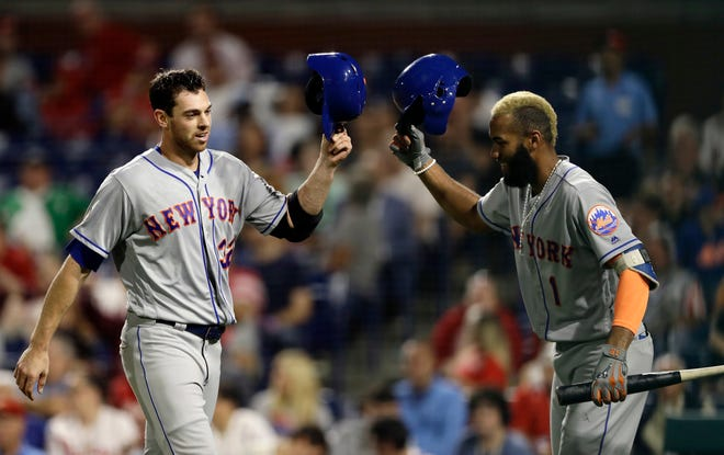 New York Mets' Steven Matz, left, and Amed Rosario celebrate after Matz's home run during the third inning of the team's baseball game against the Philadelphia Phillies, Tuesday, Sept. 18, 2018, in Philadelphia.