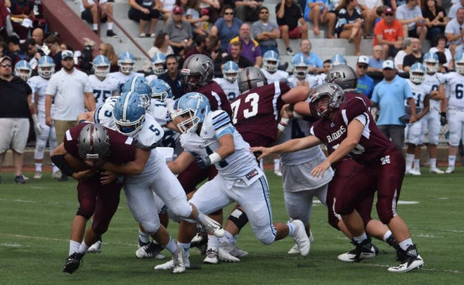 Wayne Valley's Jake DeLuccia (5) making a tackle against Nutley while Nick Trani (1) closes in.