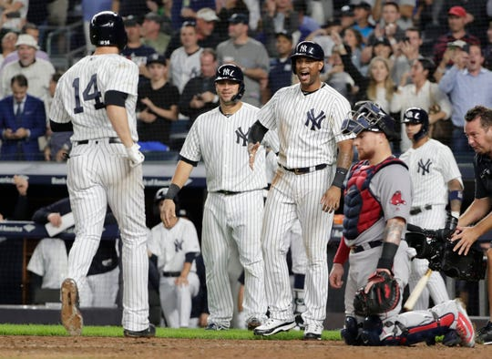 New York Yankees' Aaron Hicks, second from right, and Gary Sanchez, center, wait to greet Neil Walker (14), who passes Boston Red Sox catcher Christian Vazquez after hitting a three-run home run during the seventh inning of a baseball game Tuesday, Sept. 18, 2018, in New York.