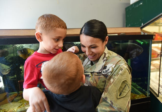 After their surprise reunion, Lt. Elise Pace (age 31), who attended the Officer Candidate School in Fort Benning, GA, talks with her two children Jonathan (age 7,in red) and Travis (age 3, foreground) at Petracco's Deli in Nutley on 09/19/18. Pace has been away four months for Army training.