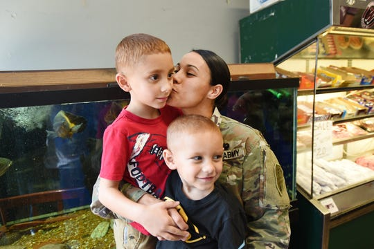 After their surprise reunion, Lt. Elise Pace (age 31), who attended the Officer Candidate School in Fort Benning, GA, kisses one of her two children, Jonathan (age 7,in red) as Travis (age 3, foreground) sits close at Petracco's Deli in Nutley on 09/19/18. Pace has been away four months for Army training.