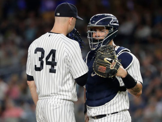 New York Yankees starting pitcher J.A. Happ (34) talks to catcher Gary Sanchez during the third inning of the team's baseball game against the Boston Red Sox on Tuesday, Sept. 18, 2018, in New York.