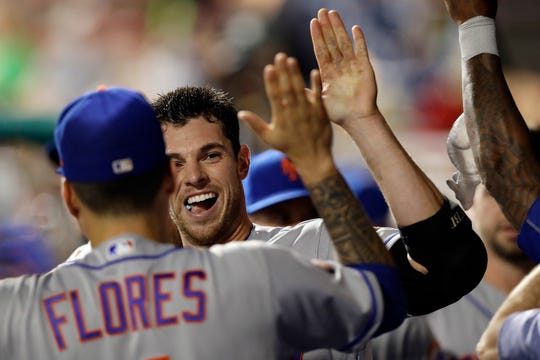 New York Mets' Steven Matz, center, celebrates with Wilmer Flores, left, and other teammates in the dugout after hitting a home run during the third inning of the team's baseball game against the Philadelphia Phillies, Tuesday, Sept. 18, 2018, in Philadelphia.