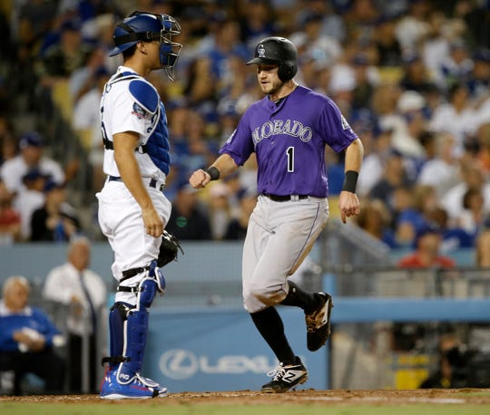 Colorado Rockies' Garrett Hampson, right, scores without a throw to Los Angeles Dodgers catcher Austin Barnes, on two-errors on a ground ball hit by DJ LeMahieu, one each by third baseman Justin Turner and left fielder Chris Taylor during the third inning of a baseball game in Los Angeles, Tuesday, Sept. 18, 2018. (AP Photo/Alex Gallardo)