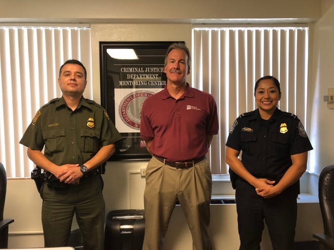 CBP Border Patrol Agent Kenneth Reza, left, NMSU Criminal Justice Department Head and professor Dennis Giever, center, and CBP officer Adriana Caranza, right, stand for a photo at Breland Hall, Room 127.