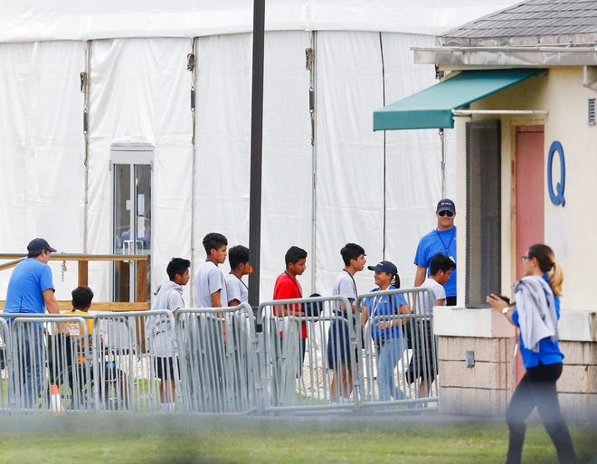 In this June 20, 2018, file photo, Immigrant children walk in a line outside the Homestead Temporary Shelter for Unaccompanied Children a former Job Corps site that now houses them in Homestead, Fla. A Senate subcommittee has found that federal officials for the second time lost track of nearly 1,500 migrant children earlier this year after a government agency placed the minors in the custody of adult sponsors in communities nationwide.