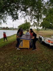 Eunice Youth Advisory Council install the new duck house they constructed at Eunice Lake as part of the 9/11 Day of Service 2018.