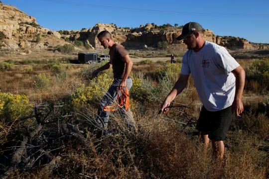 Allen Elmore, left and Cody DeClusin members of Cliffhangers Four Wheel Drive Club search for trash during a cleanup project for National Public Lands Day, Saturday, Sept. 26, 2015 in the Glade Run recreation area in Farmington.