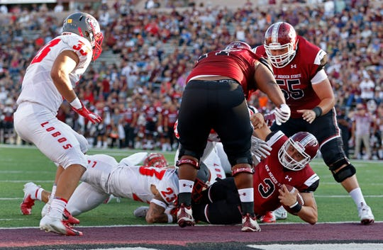 New Mexico State quarterback Matt Romero (3) lunges over the goal line to score a touchdown during the first half of an NCAA college football game against New Mexico in Las Cruces, N.M., Saturday.