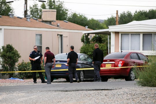 Farmington police Sgt. Albert Boognl, left, talks with detectives while investigating a shooting today on the 1000 block of Hollywood Street in Farmington.