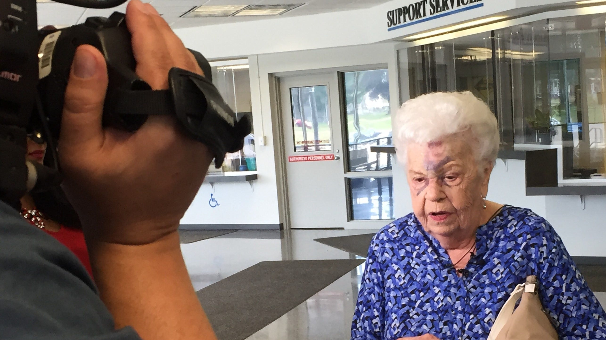 Gloria Kevelighan, 88, speaks to the media Wednesday about being attacked and robbed of her purse and her vehicle outside a Livonia Walmart on Tuesday. Kevelighan was badly bruised in the assault; police have two people in custody.