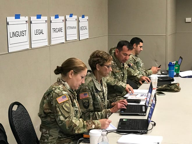 Personnel at the Joint Repatriation Processing Center at Ontario Convention Center.