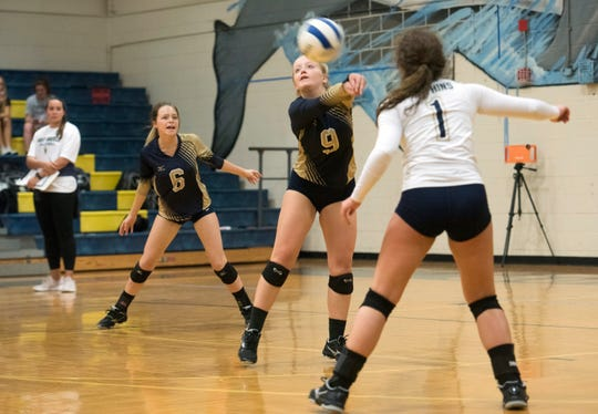 Gulf Breeze High School's Olivia Boling, (No.9) dig a Catholic serve as teammates, Rilee Sabik, (No. 6) and Sophia Doerr, (No. 1) standby to assist during Tuesday's match against the Crusaders.