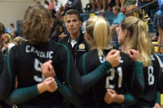 Catholic High Volleyball coach, Giulio Simonelli, gives his plays a few tidbits of advice before the start of Tuesday's match against, Gulf Breeze.