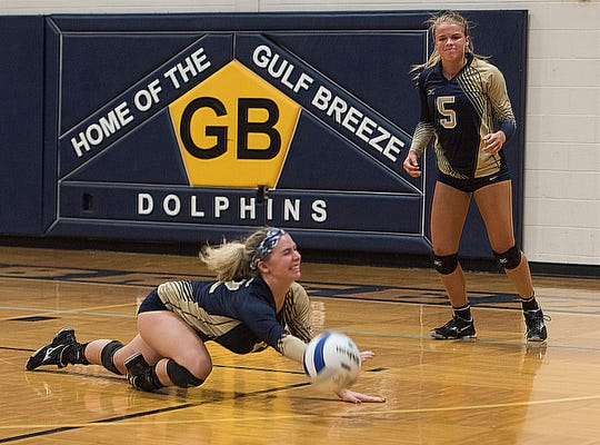 Gulf Breeze High's Madison Clay,(No. 12) comes up short on the dig as teammate Kennedy Hooten, (No. 5) looks on during Tuesday night's volleyball match against Catholic.