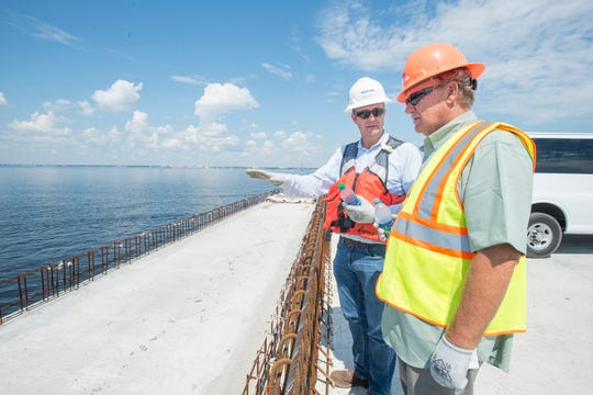 State Sen. Doug Broxson, right, listens Wednesday as Tom Fulton, Skanska vice president of operations and project director, points out features of the new Pensacola Bay Bridge during a tour.