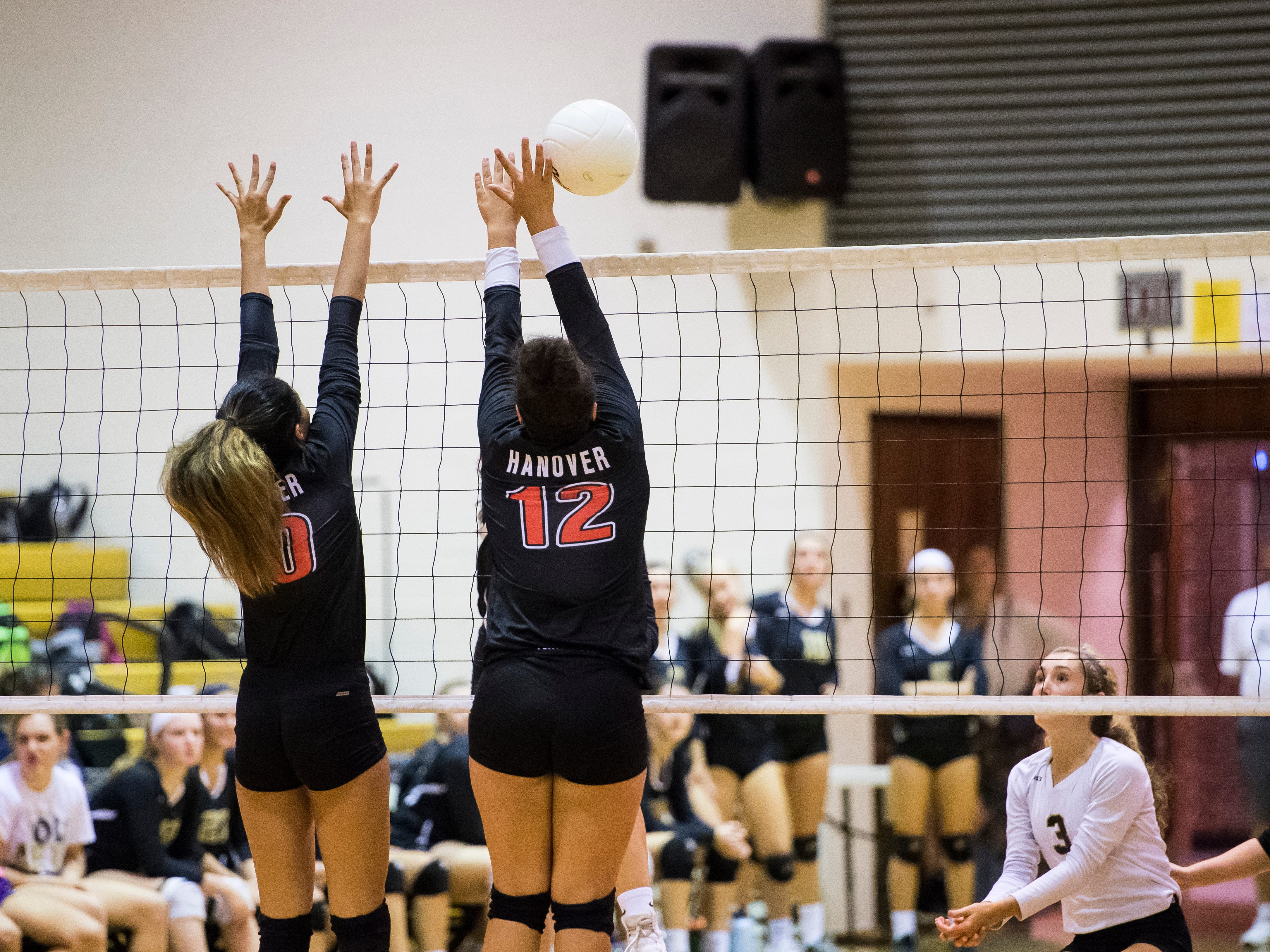 Hanover's Nakhaiya Jacobs (12) and Nancy Hernandez jump to attempt a block against Delone Catholic on Tuesday, September 18, 2018. The Squirettes swept the Hawkettes 25-16, 25-19, 25-14.