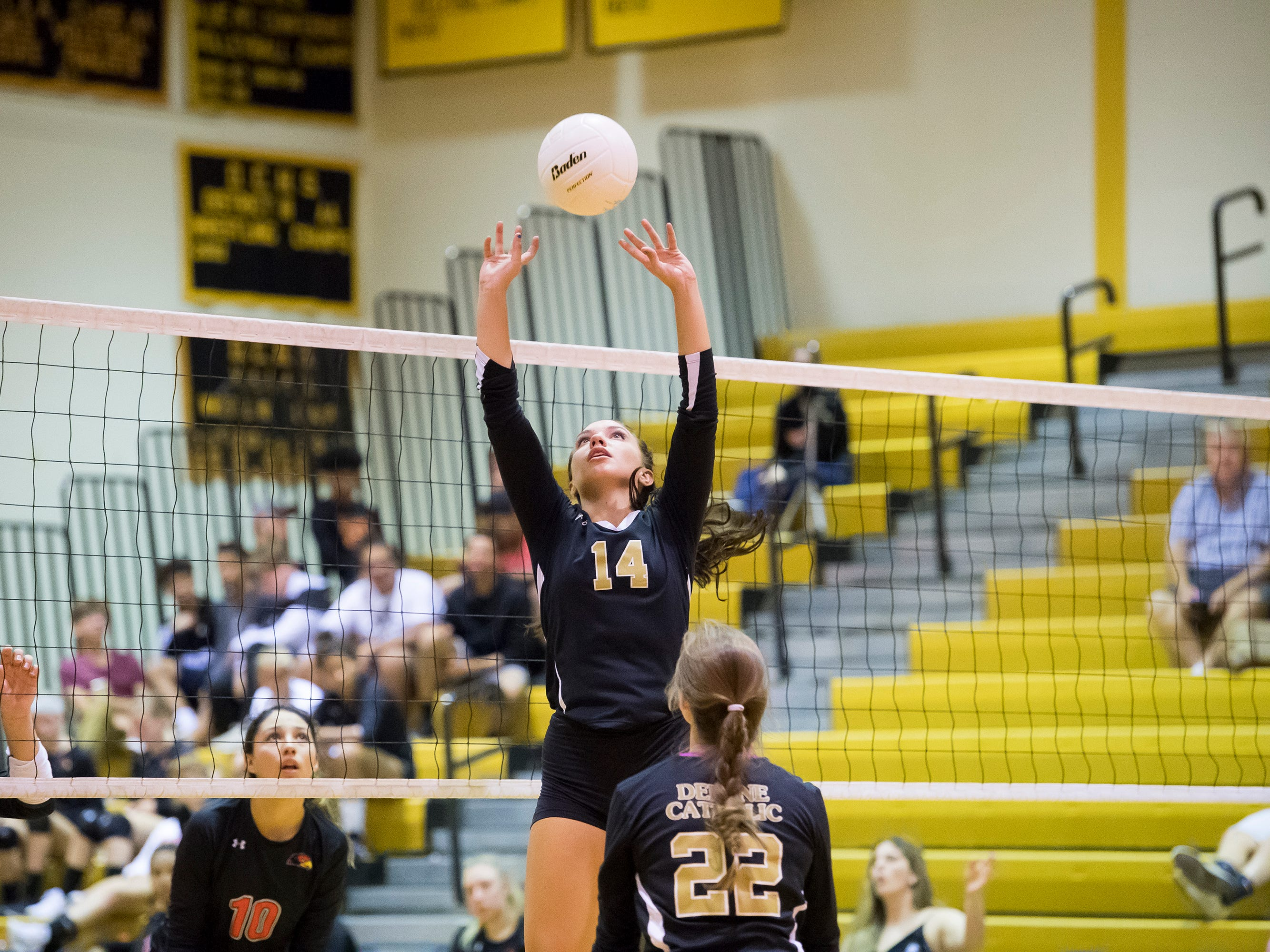 Delone Catholic's Molly Raville sets the ball for teammate Emily Miller (22) during play against Hanover on Tuesday, September 18, 2018. The Squirettes swept the Hawkettes 25-16, 25-19, 25-14.