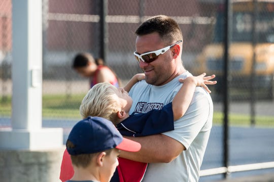 New Oxford girls tennis head coach Travis Martin greets his two sons, Brady, 5, and Bryce, 8, during a recent tennis match.