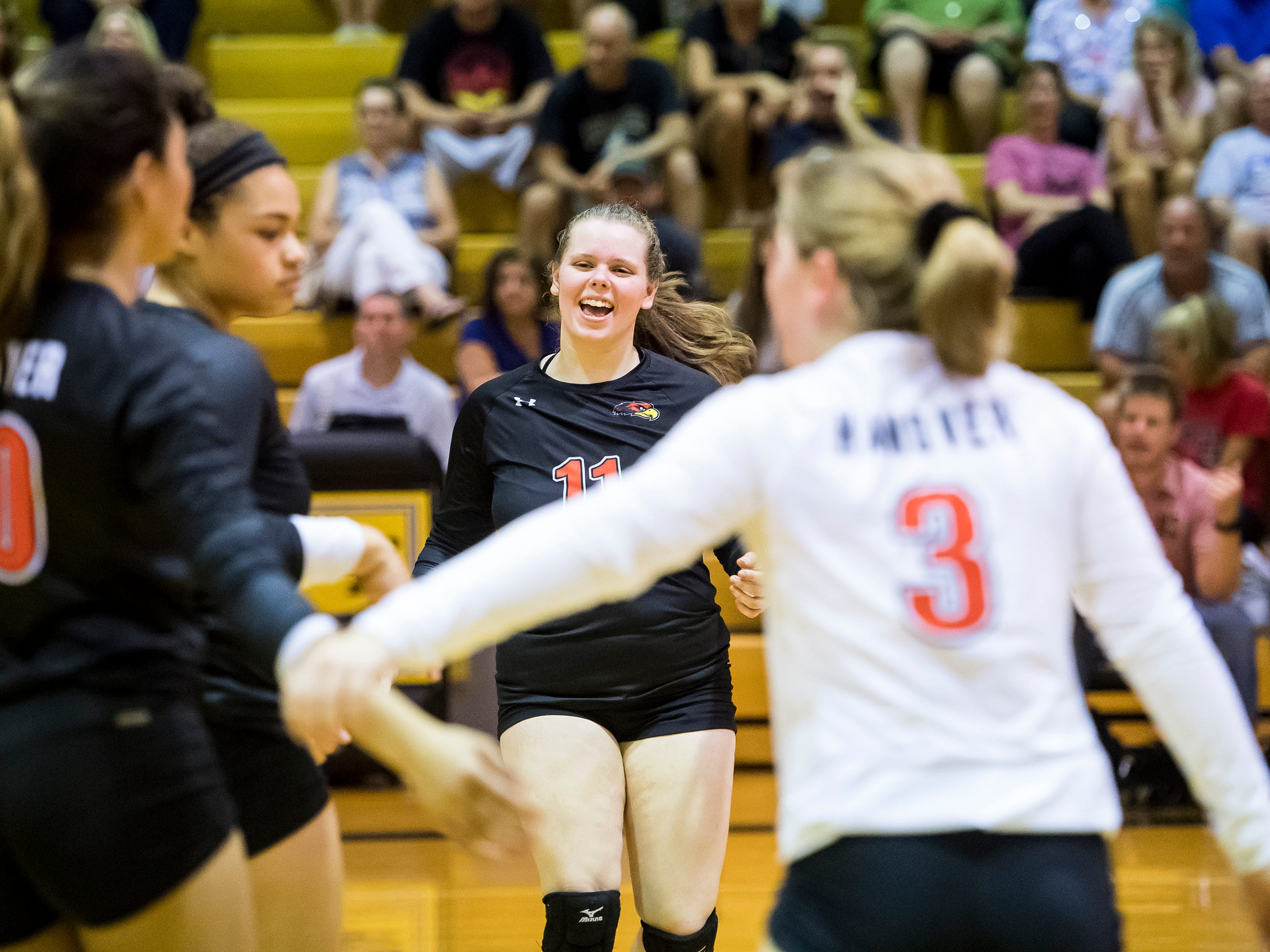 Hanover's Savannah Disney (11) celebrates a point with her teammates during play against Delone Catholic on Tuesday, September 18, 2018. The Hawkettes fell in three straight sets;  25-16, 25-19, 25-14.