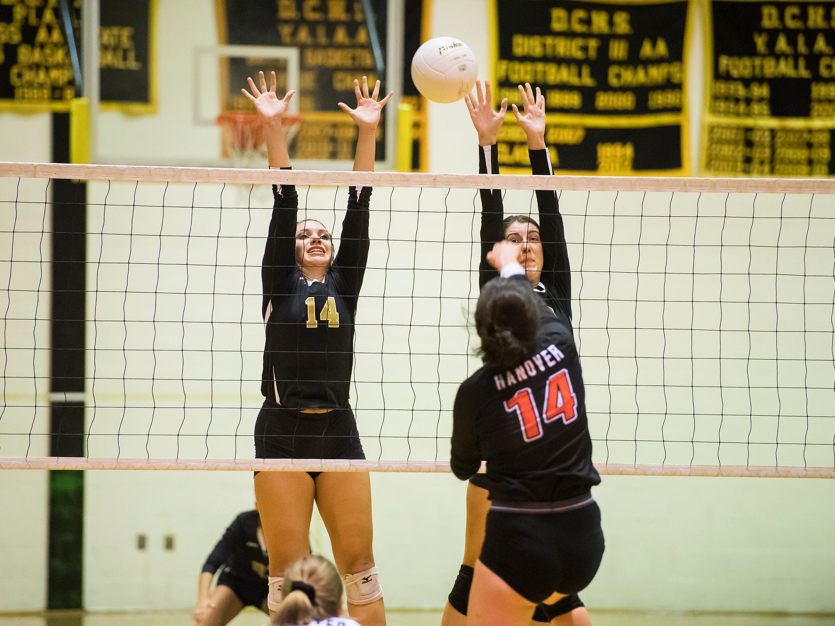 Delone Catholic's Molly Raville (14) and Ava Bunch attempt to block a shot from Hanover's Allyson Montour on Tuesday, September 18, 2018. The Squirettes swept the Hawkettes 25-16, 25-19, 25-14.