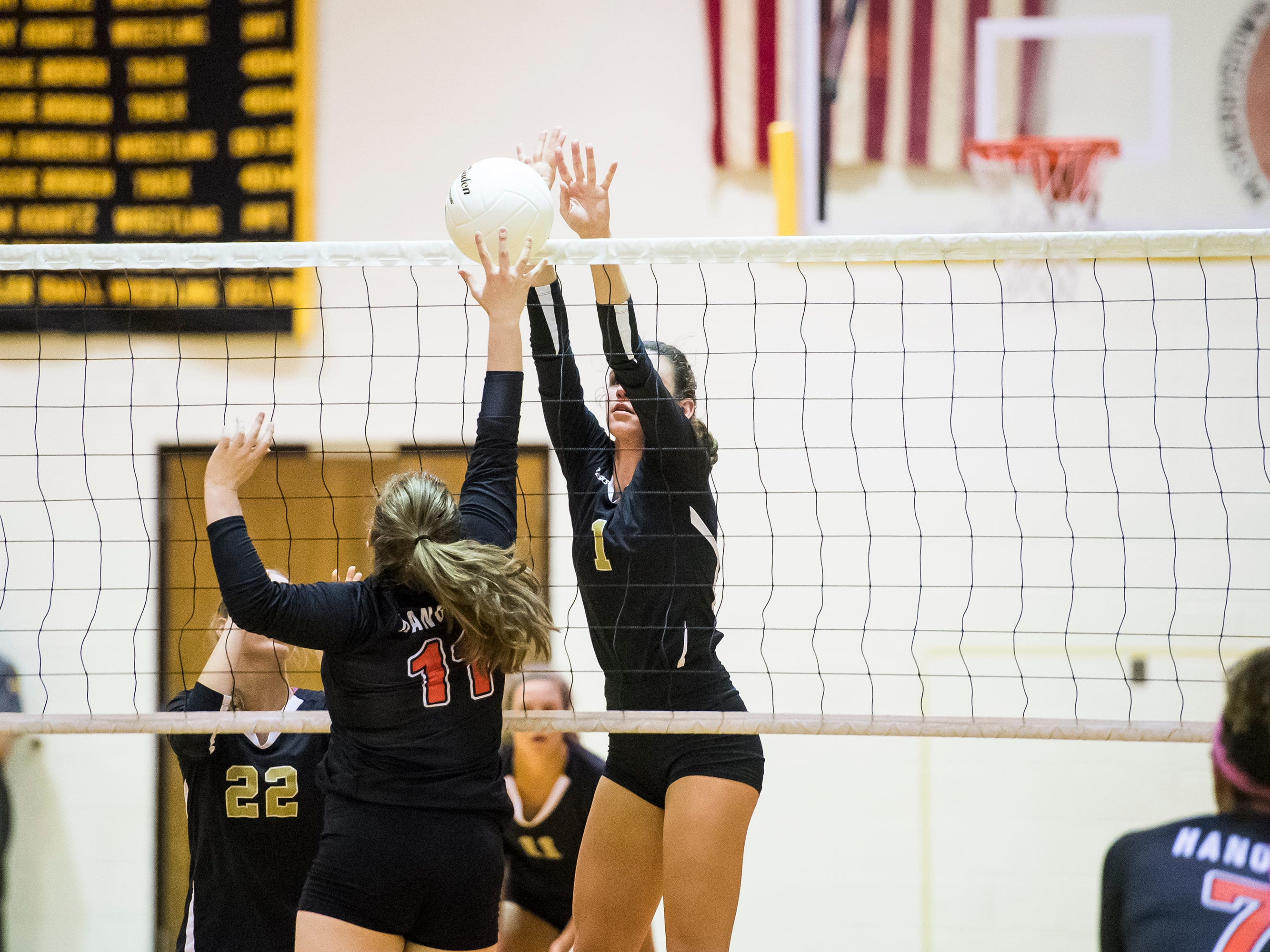 Delone Catholic's Maddie Clabaugh (1) blocks a shot from Hanover's Savannah Disney on Tuesday, September 18, 2018. The Squirettes swept the Hawkettes in three sets; 25-16, 25-19, 25-14.