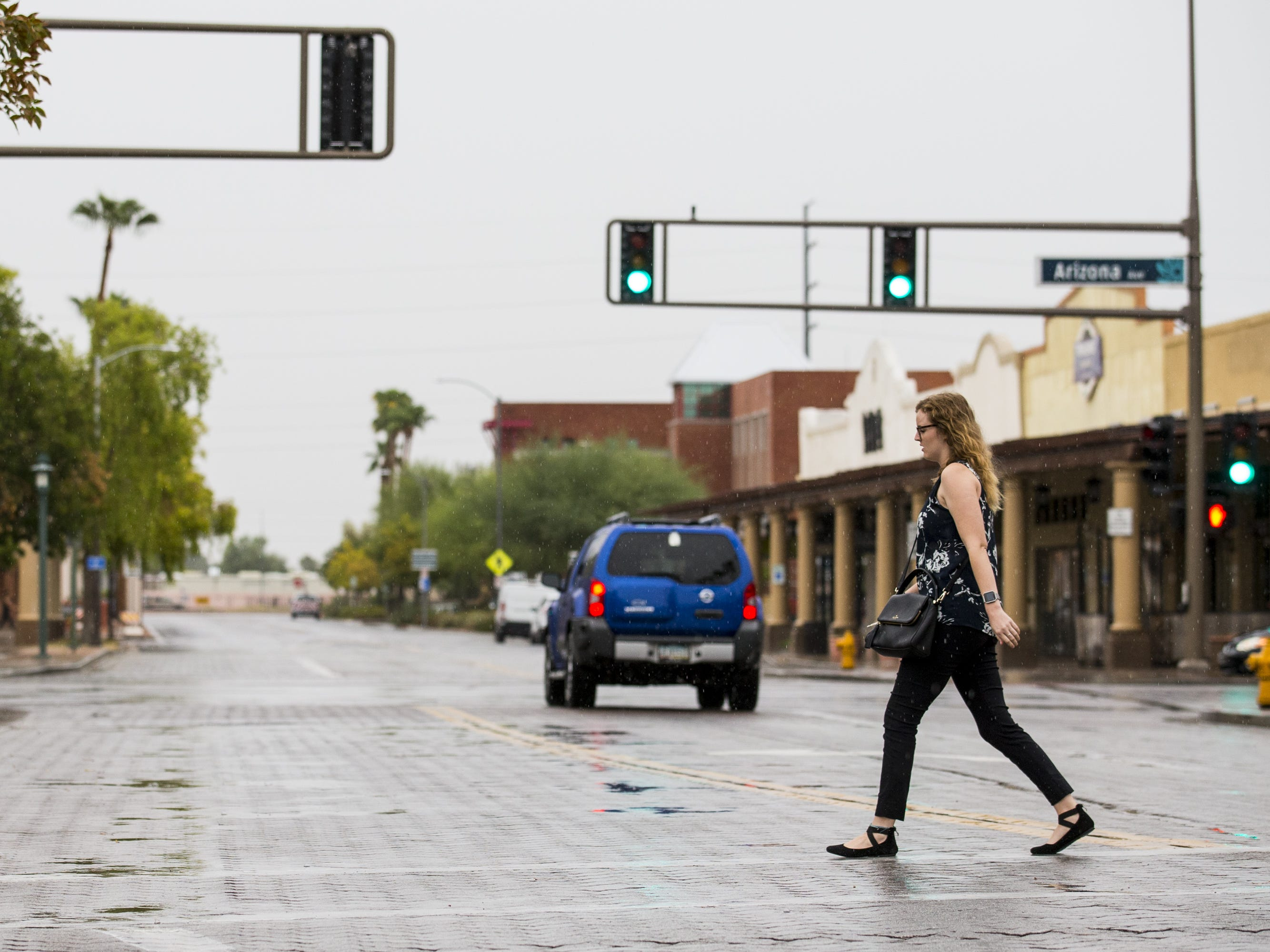 A woman walks across the street in the rain on Sept. 19, 2018, in Chandler.