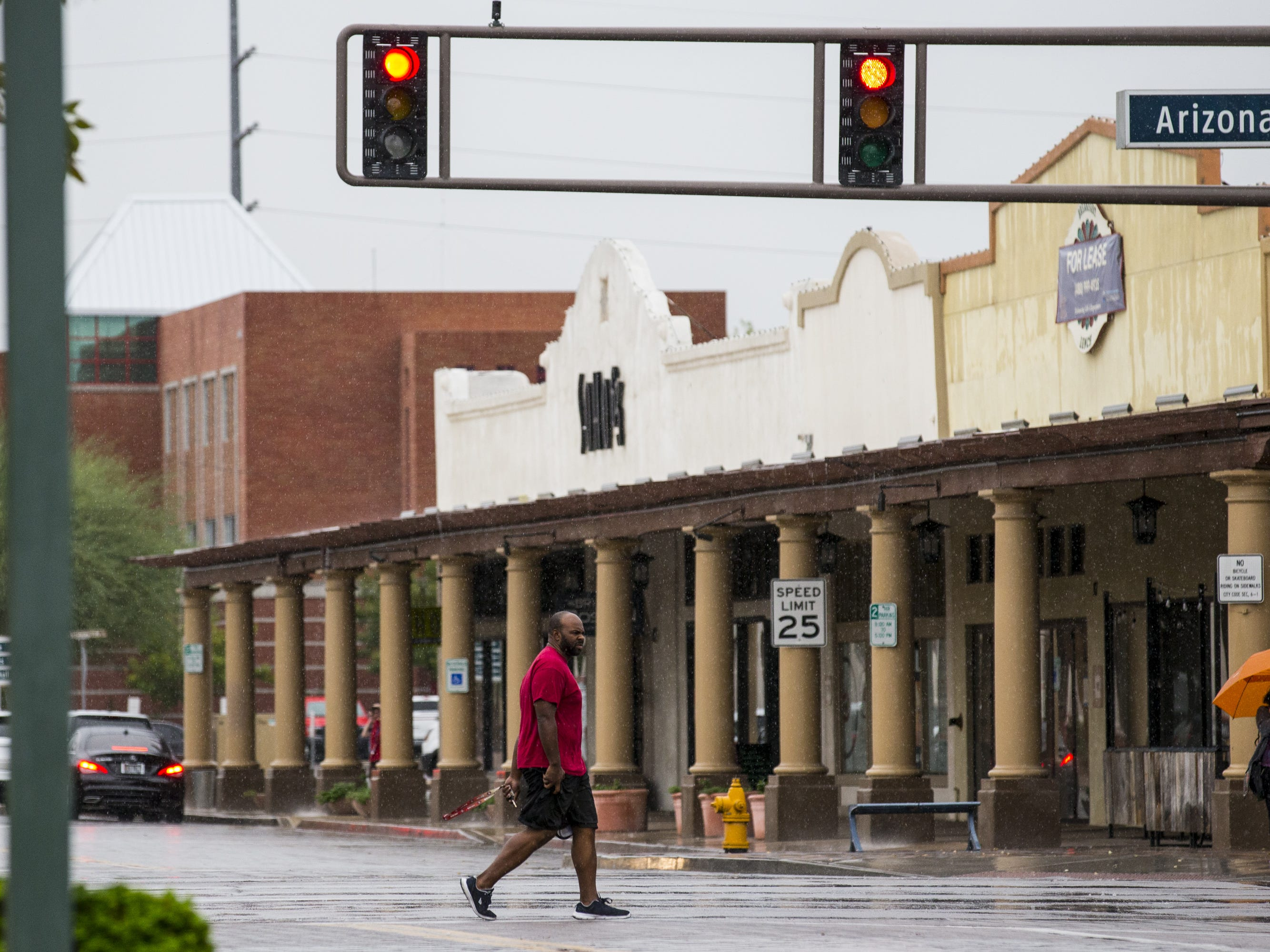 A man walks across the street in the rain on Sept. 19, 2018, in Chandler.