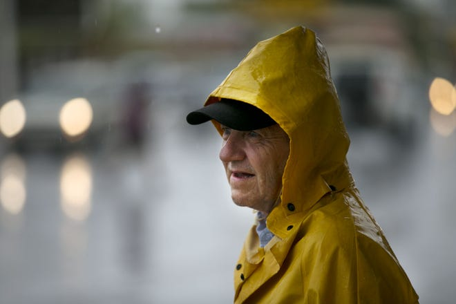 Steve Fishleigh of Phoenix waits for a bus in the rain near Thomas Road and 32nd Street in Phoenix on Sept. 19, 2018.