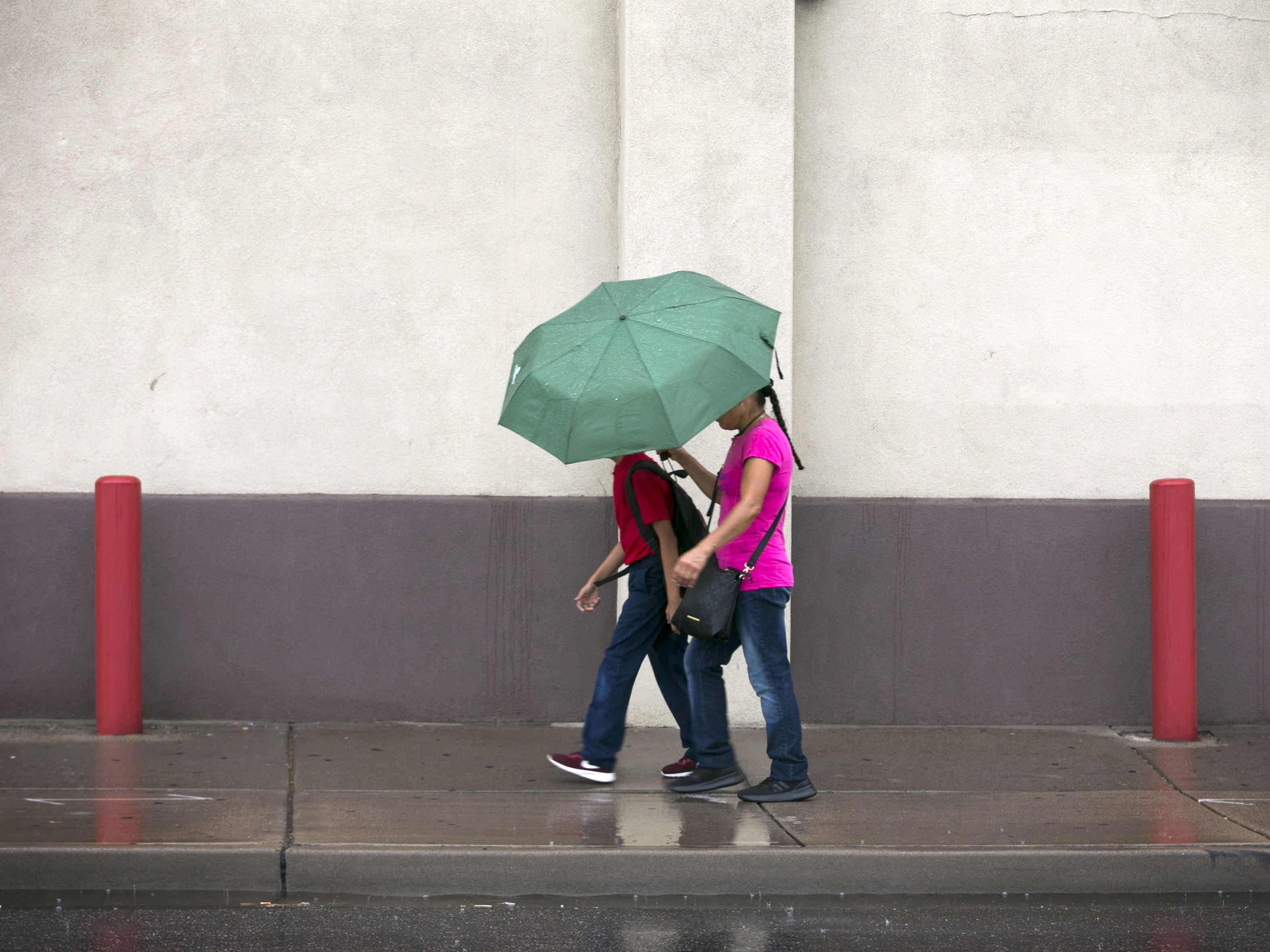 Pedestrians stay dry under their umbrella while walking in the rain along McDowell Road near 24th Street in Phoenix on Wednesday, September 19, 2018.