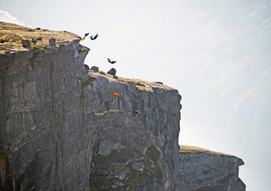 Not only people willing to jump off a cliff, but happy to pay for the opportunity. Base jumpers hurl themselves off Kjeragbolten rock in Rogaland, Norway. Canon 5D.