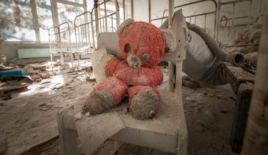 Old red teddy bear sitting on a chair in an abandoned kindergarten in Pripyat, a reminder of the 1986 Chernobyl disaster.