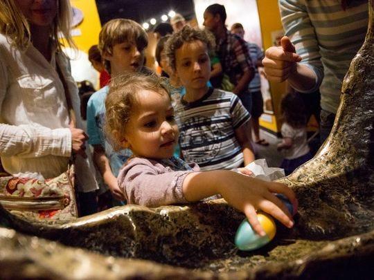 Mila Houssameddine (centro) devuelve un huevo después de haber agarrado dos durante la Cacería de Huevos Dino en el Museo de Historia Natural de Arizona el viernes 25 de marzo de 2016 en Mesa, Arizona.