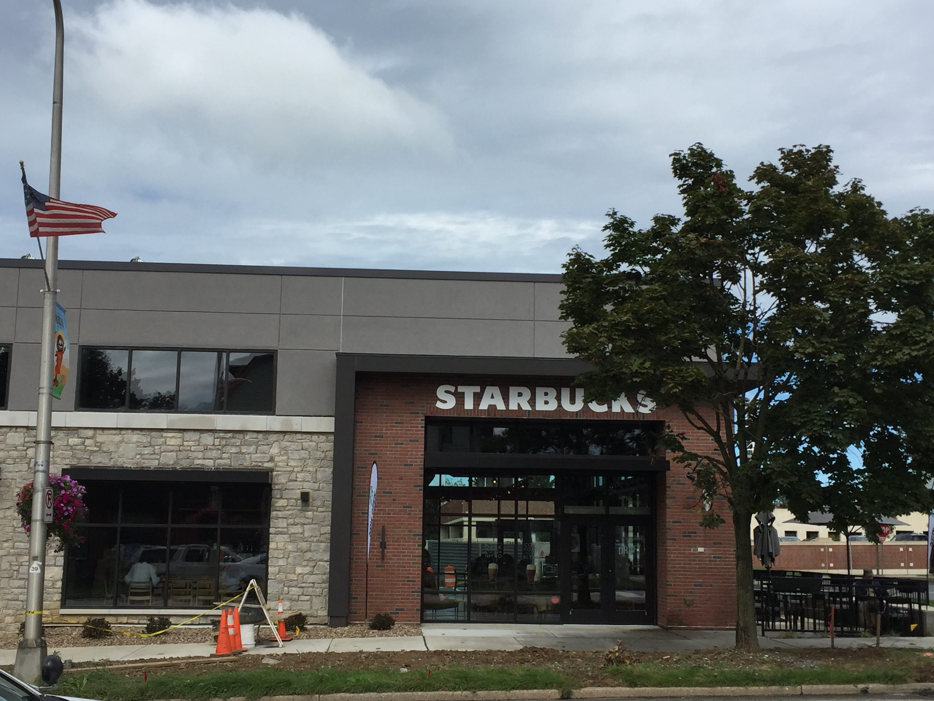 A Great Clips will eventually open next door to Starbucks, which has a cozy outdoor patio visible on the right.
