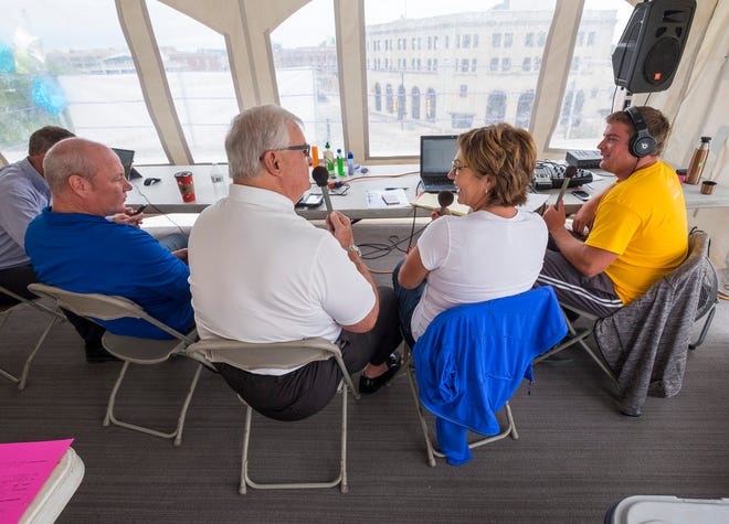 Q Country 107 WSAQ host Matt Markham, right, talks on the radio with St. Clair County CMH director Deb Johnson, second from right, Paul Maxwell, second from left, and St. Clair County Sheriff Tim Donnellon Wednesday, Sept. 19, 2018, during the Community Roof-Sit for Kids' Rooftop Rally.