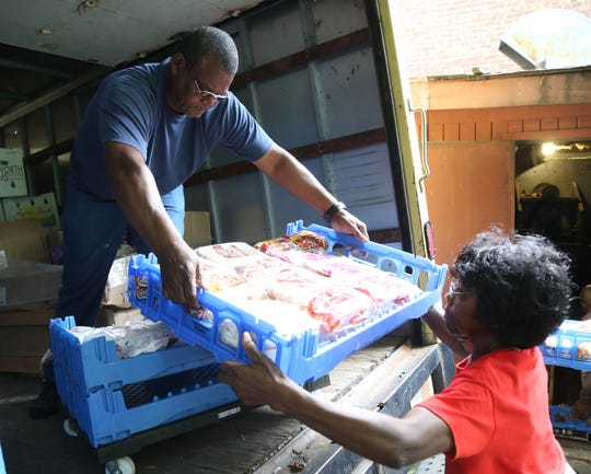 Nigel Barnett hands a tray of bread to Janie Busby as part of a food delivery for the Trinity Temple Seventh Day Adventist Food Pantry in the City of Poughkeepsie on September 19, 2018.