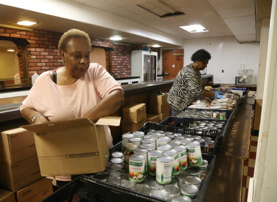 Volunteers, from left, Gwen Spencer and Elma Faye John stock tables at the Trinity Temple Seventh Day Adventist Food Pantry in the City of Poughkeepsie before they open for busines on September 19, 2018.