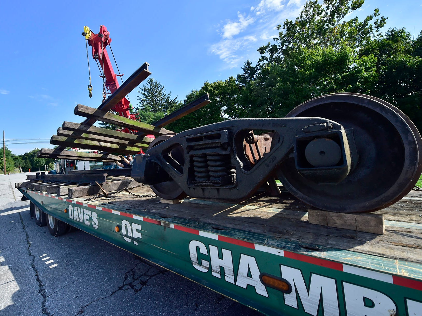 Dave's Trucking workers collect a railroad car on Wednesday, September 19, 2018 to move it to Shippensburg.The 93-year-old railroad car that had a home in the parking lot at Hood and King Street, will be relocated near the steam plant in Shippensburg to be part of a museum highlighting the history of Shippensburg University's use of coal.The county has purchased the parking lot for employee parking.