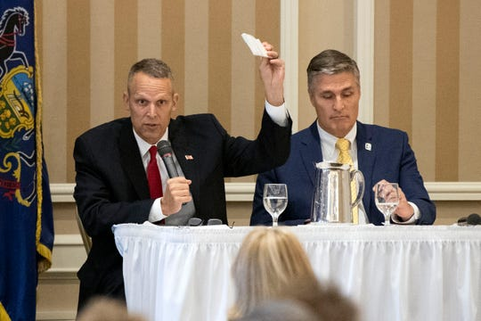 U.S. Rep. Scott Perry, R-York County, left, holds up the U.S. Constitution during a debate with Democratic challenger George Scott, right, at the Country Club of York on Wednesday. They spoke before the Rotary Club of York. The incumbent and challenger are competing for the new 10th Congressional District, whose boundaries encompass the cities of Harrisburg and York.