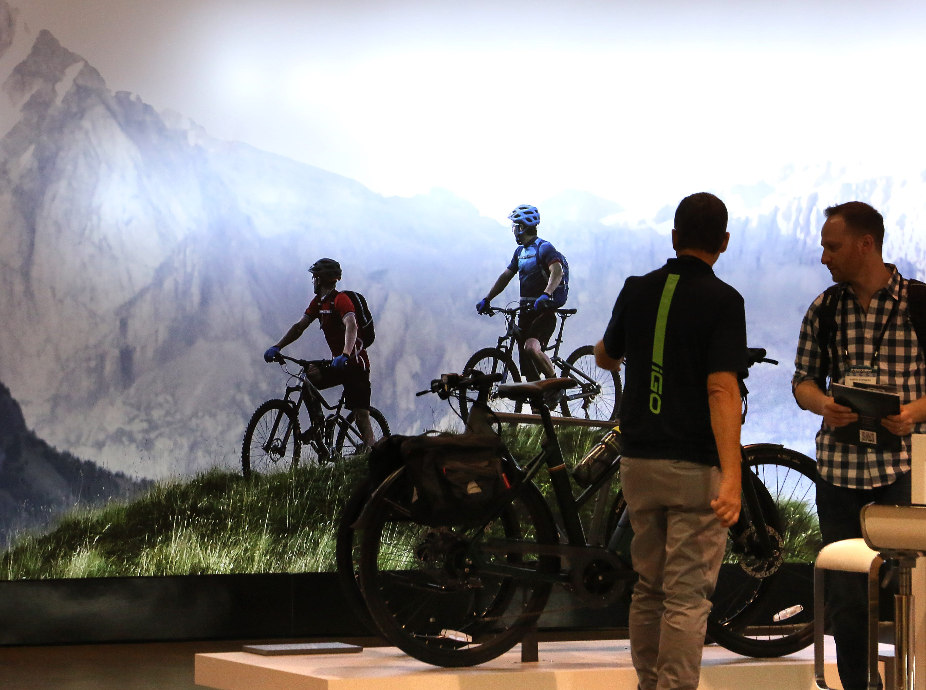Attendees are seen in front of a mountain bike mural at the Interbike Expo at the Reno-Sparks Convention Center in Reno on Sept. 19, 2018.