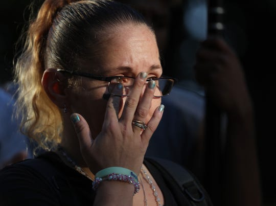 """Amandia Youngs, daughter of Robert  """"Bobby"""" Burrows, wipes a tear from her eye during a memorial service in Washington Square Park where her father passed away."""