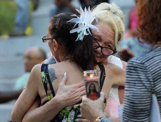 """April Zimmerman, sister of Robert """"Bobby"""" Burrows, hugs Burrows' girlfriend Anna Dalessandro during a memorial service for him."""