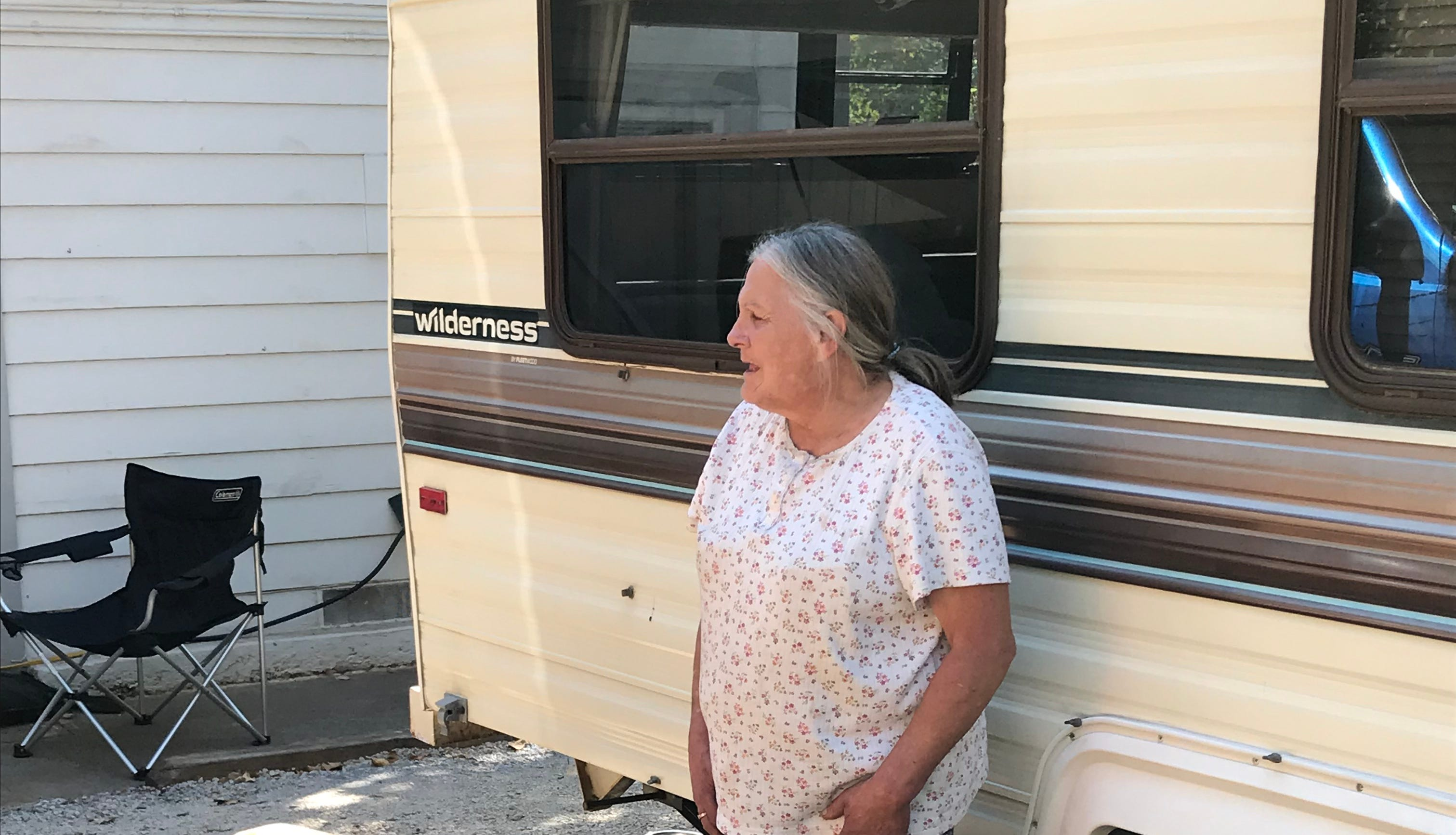 Lynn Adams and her dogs Scamp, right, and Dutchess, left, outside the donated fifth wheel in Redding.