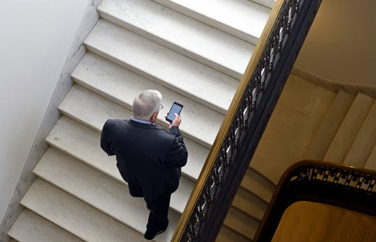 In this Feb. 4, 2015, file photo, Sen. Mike Enzi, R-Wyo., checks his phone as he arrives for a bipartisan lunch in the Kennedy Caucus Room on Capitol Hill in Washington. Oregon Sen. Ron Wyden is proposing new legislation that would allow the Senate's Sergeant at Arms to spend taxpayer money protecting senators' private email accounts and personal devices amid persistent anxieties over the digital security of the American midterm vote.