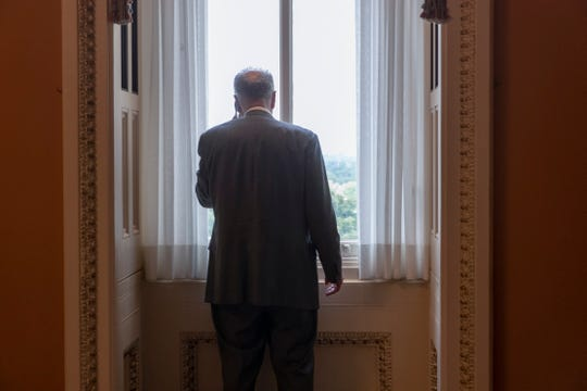 In this Aug. 1, 2018, file photo, Senate Minority Leader Chuck Schumer, D-N.Y., makes a phone call just off the Senate floor on Capitol Hill in Washington. Oregon Sen. Ron Wyden is proposing new legislation that would allow the Senate's Sergeant at Arms to spend taxpayer money protecting senators' private email accounts and personal devices amid persistent anxieties over the digital security of the American midterm vote.