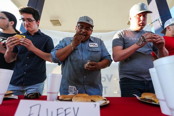 Contestants eat during the Cheeseburger Eating Championship on Tuesday, Sept. 18, 2018, at Lonestar Cheeseburger.