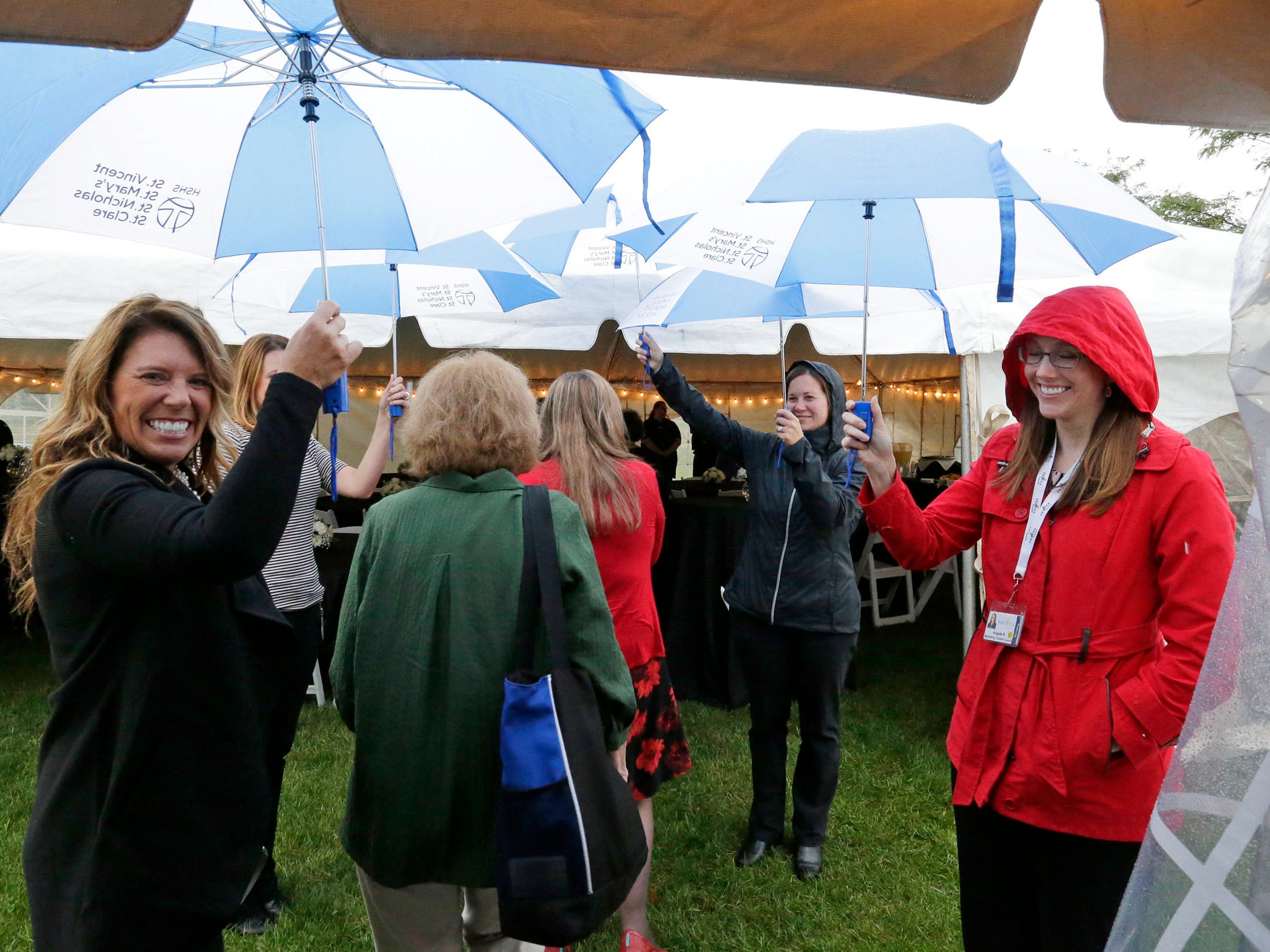 People walk to a reception tent under umbrellas at HSHS St. Nicholas Hospital during a Mass of Celebration for the new CEO Justin Selle, Wednesday, September 19, 2018, in Sheboygan, Wis.